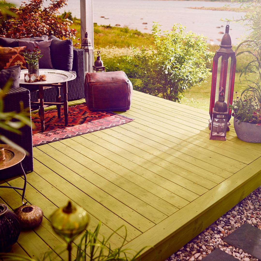 en flott terrasse ved et vann med masse grønne planter