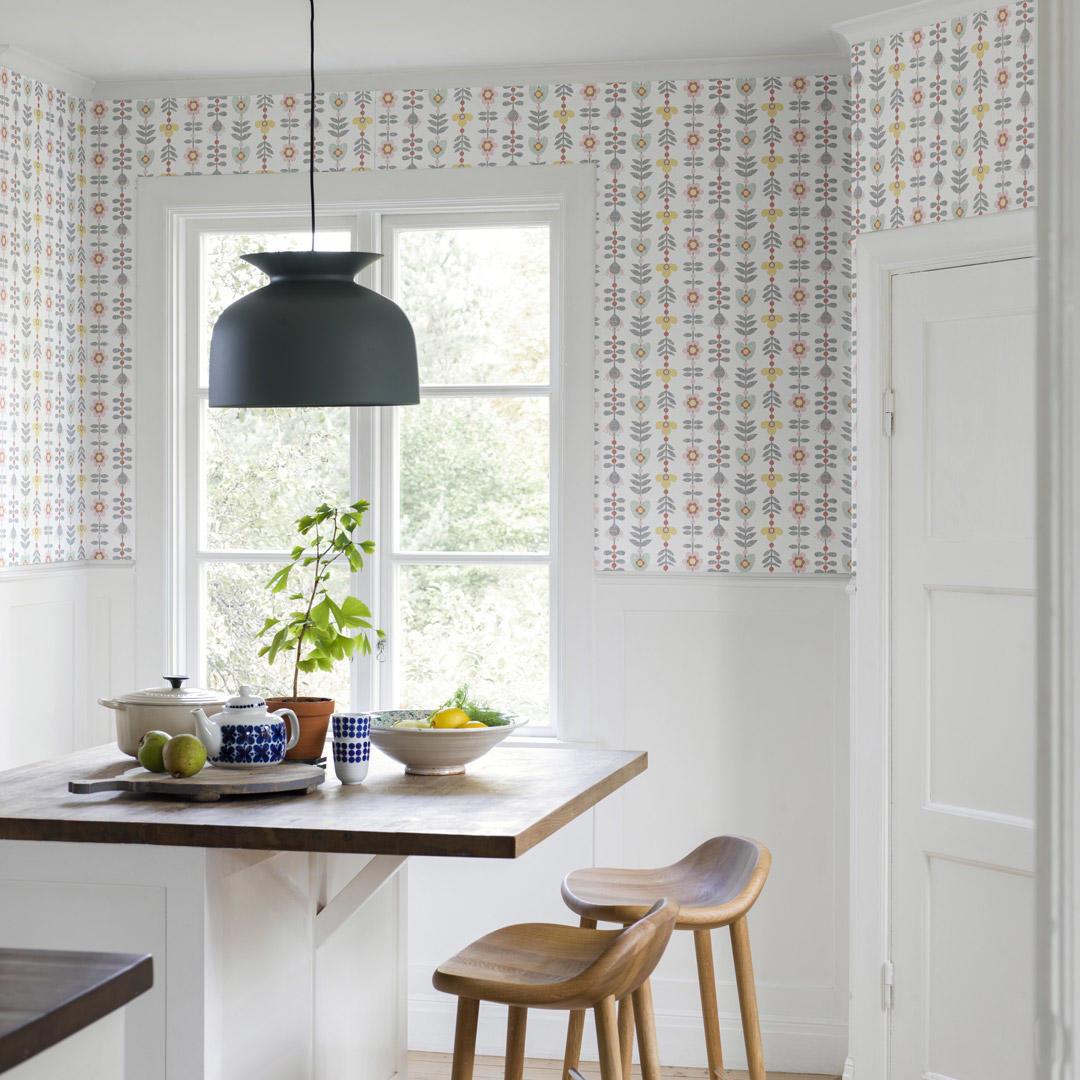 Et hvit kjøkken med grafisk tapet på vegen og stor grå taklampe over bordet