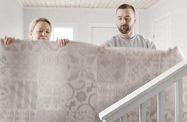 en kvinne og en mann holder opp et vinylgulv