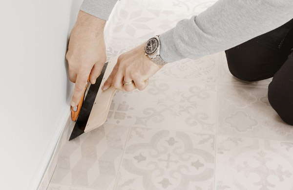 en sparkel blir holdt mot veggen og vinylgulvet under blir skåret